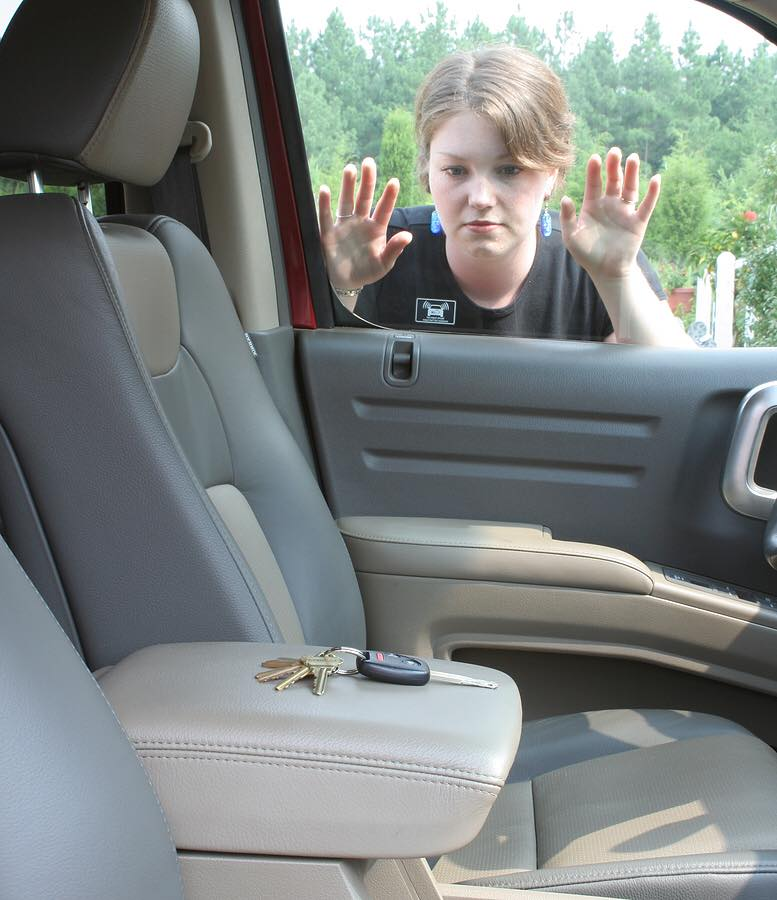 image of a woman looking at the keys she's locked inside her car.